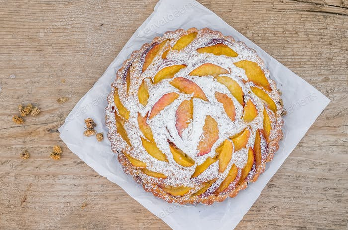Peach pie with sugar powder over a peace of paper