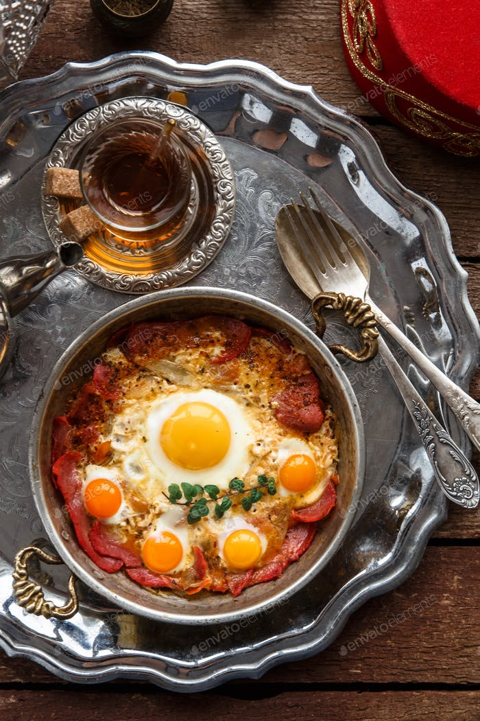 Turkish cured beef and fried eggs in copper pan, traditional breakfast, top view