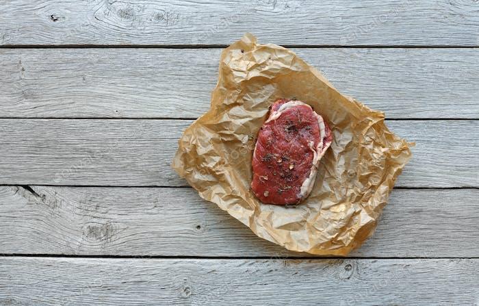 Rohes Rindfleischsteak auf dunklem Holztischhintergrund, Draufsicht