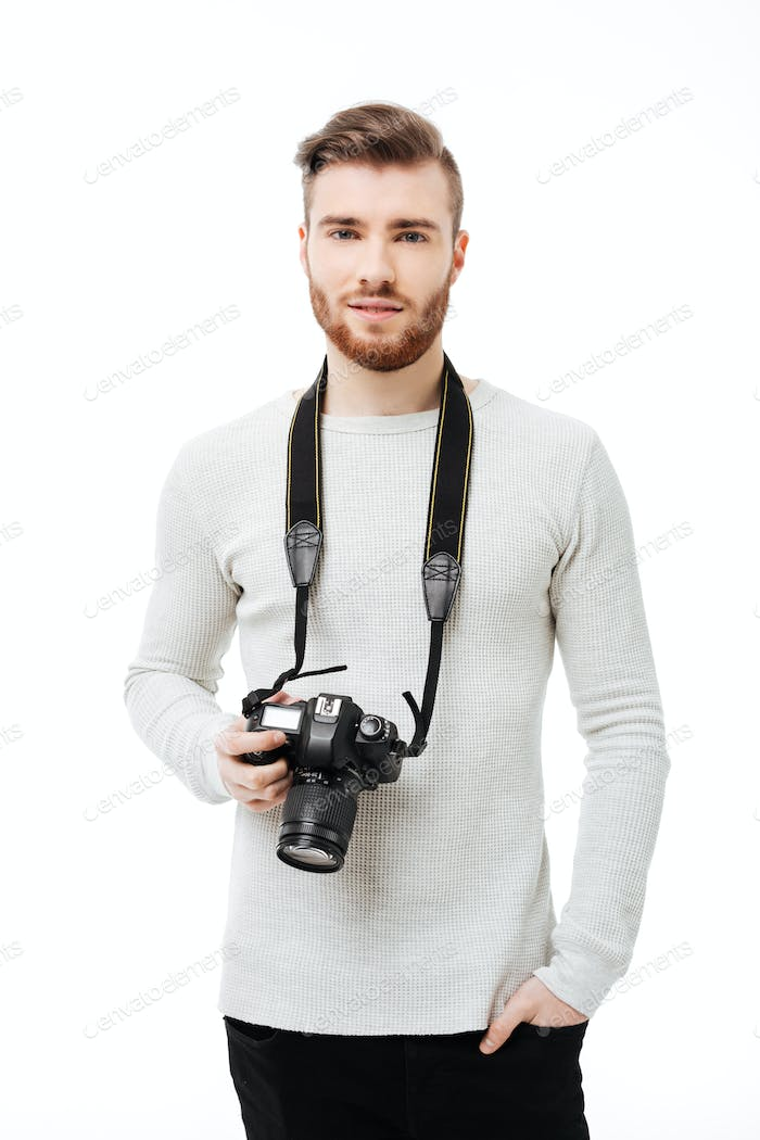 Handsome bearded young man looking at the camera with DSLR camera hanging on neck isolated
