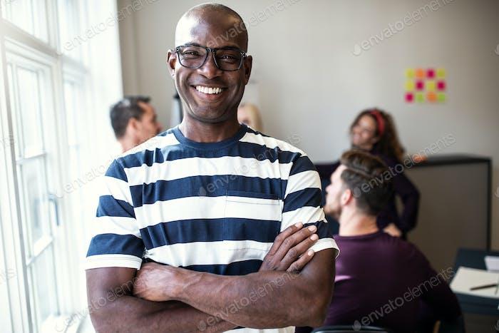 Afrikanischer Designer lächelnd selbstbewusst nach einem Bürotreffen