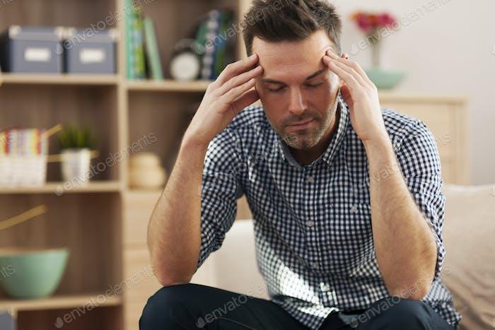 Handsome man sitting on sofa with big headache