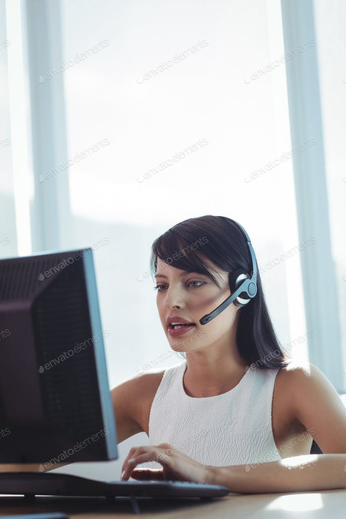 Businesswoman talking on headset while working at call center