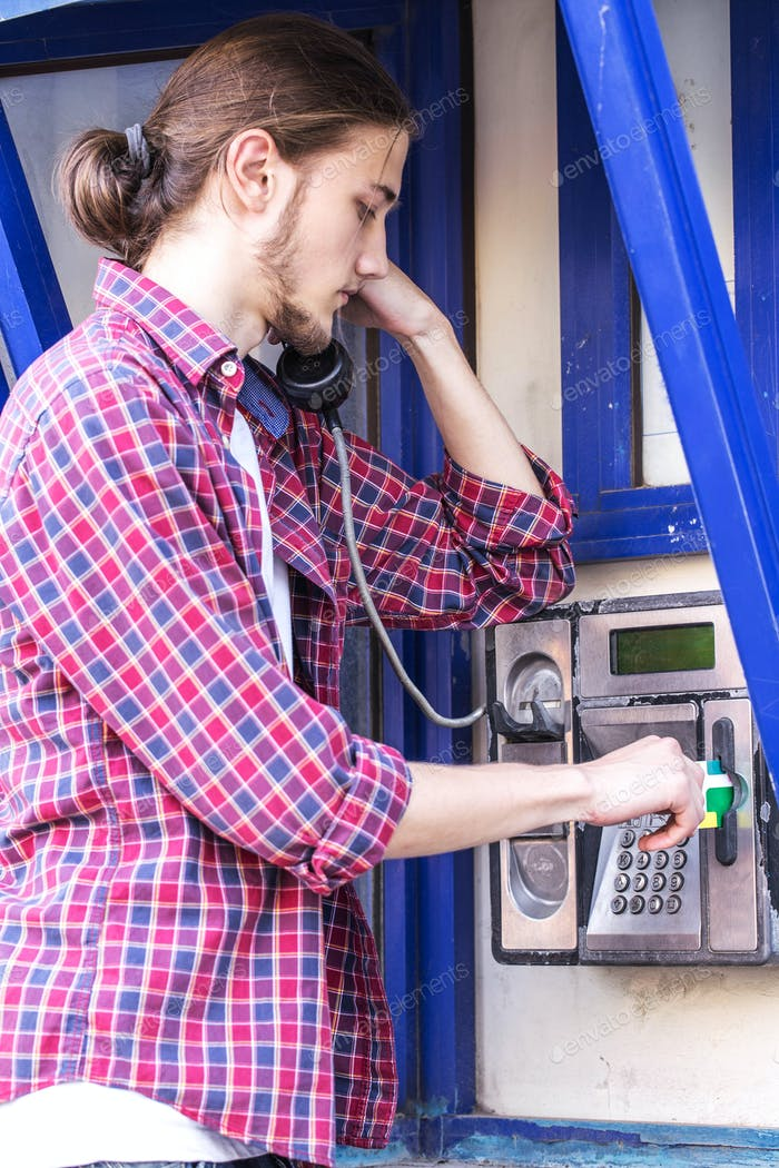 Man puts call card on public phone.