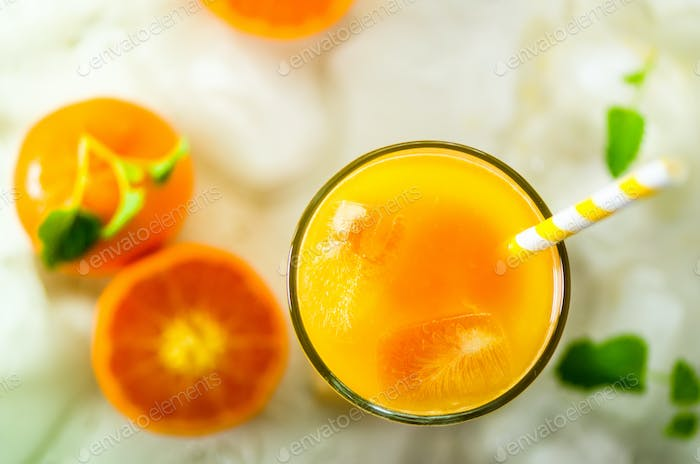 Fresh orange juice in glass and tangerines with mint, ice on white background. Top view, copy space
