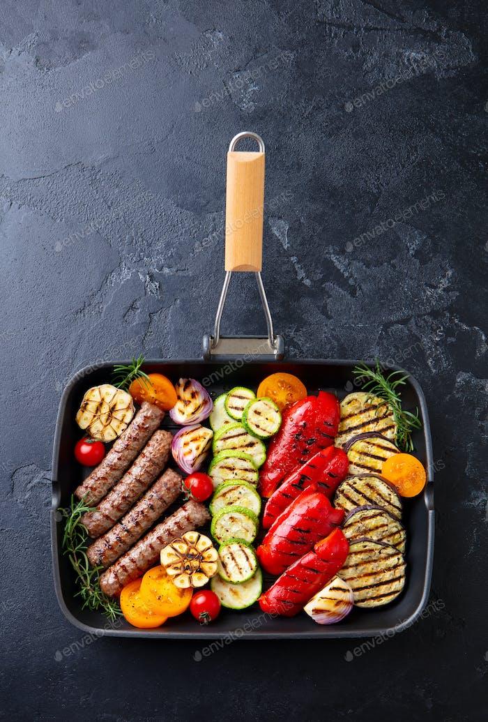 Gegrilltes Fleisch Kebab und Gemüse in Grillpfanne. Schwarzer Stein Hintergrund. Draufsicht.