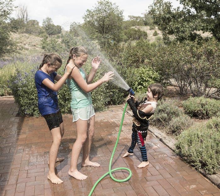 Kinder, die sich gegenseitig mit Wasserschlauch besprühen