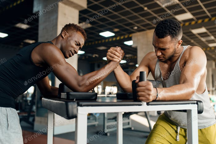 Two men fighting, arm wrestling training in gym