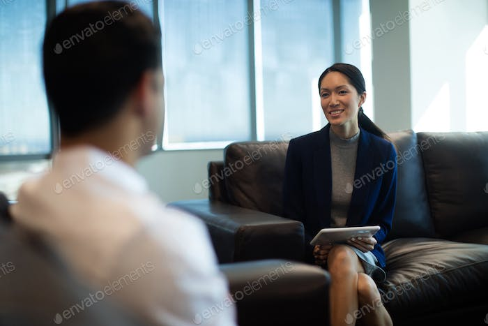 Businesswoman holding digital tablet while discussing with male colleague