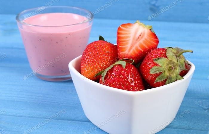 Fresh strawberries and delicious milkshake on blue boards, healthy dessert