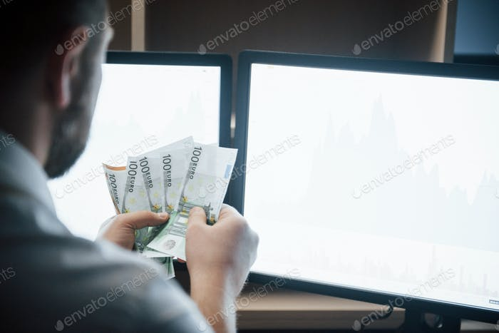 Bearded man in white shirt holds earned money in the office with multiple computer screens