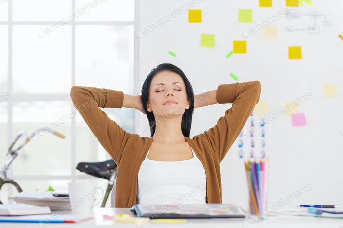 Business woman relaxing. Business woman relaxing with hands behind head and smiling