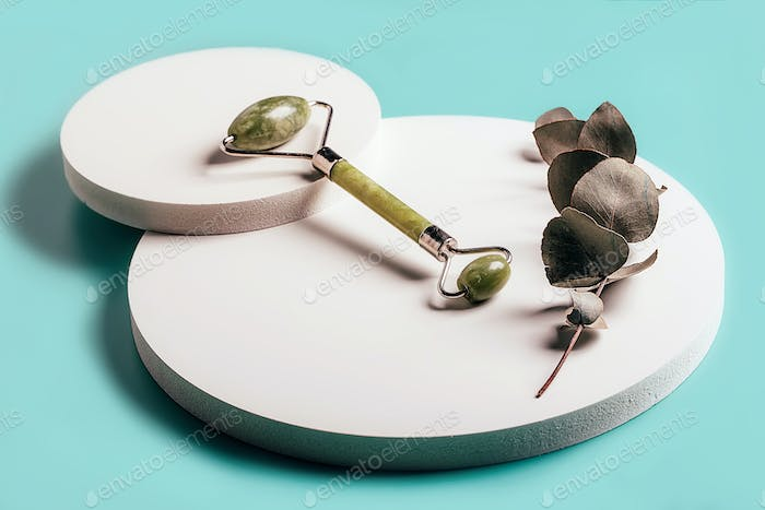 Facial crystal stone roller massager and eucalyptus branch on white round boards.