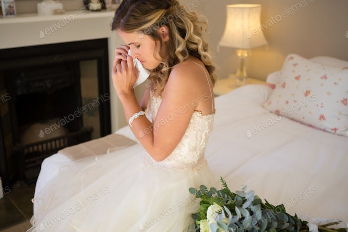 Sad bride crying while sitting on bed