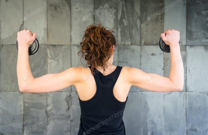 Вид сзади молодой девушки, поднимающей гантели диски