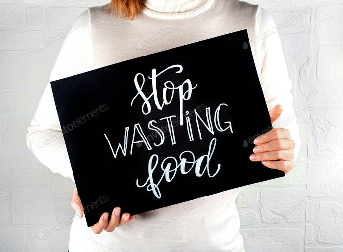 Woman keeping a small chalkboard with Stop Wasting Food lettering