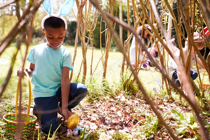 Group Of Children Wearing Bunny Ears Finding Easter Eggs Hidden In Garden