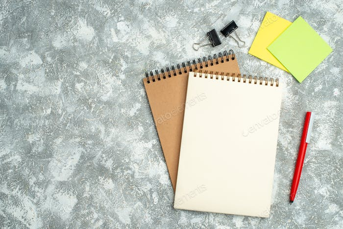 Top view of two kraft spiral notebook with pen colorful notepapers on ice background
