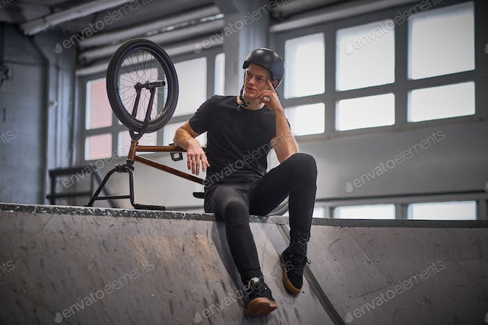 Bmx rider relaxing after practicing tricks with his bike in a skatepark indoors