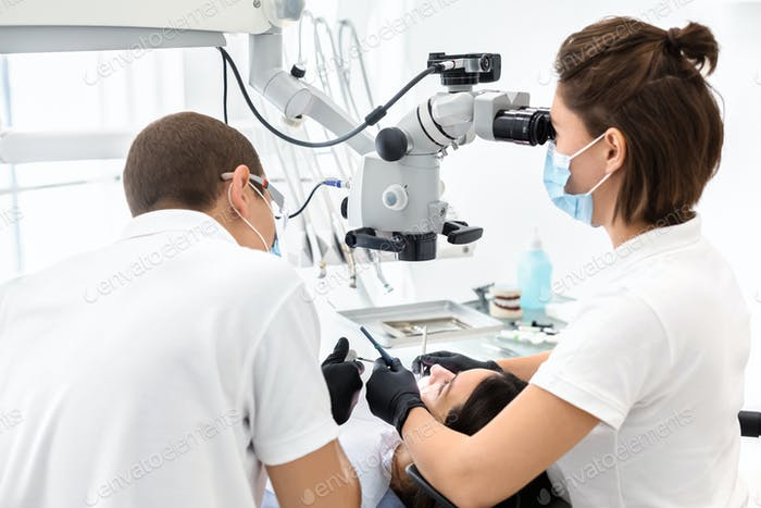 Two dentists making treatment in modern dental clinic
