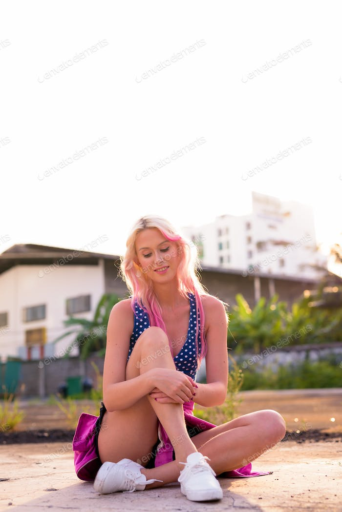 Happy young beautiful blonde woman sitting in the streets outdoors