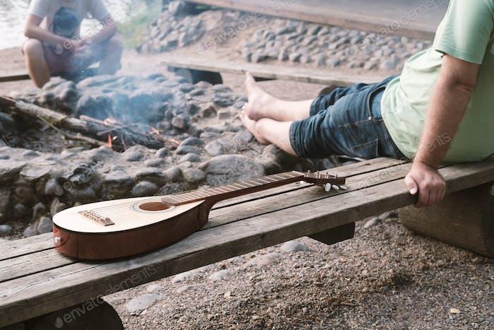 Entspannter Mann sitzt auf einer Holzbank am Feuer, als nächstes ist eine Gitarre