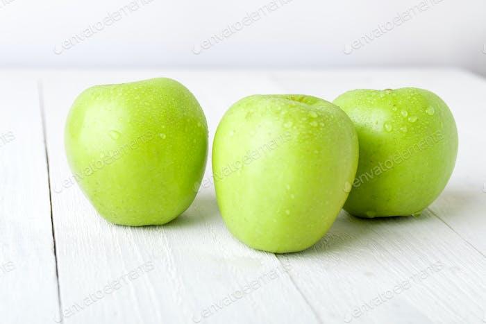 Three wet green apples