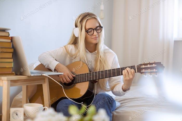 Mädchen spielen Gitarre zu Hause