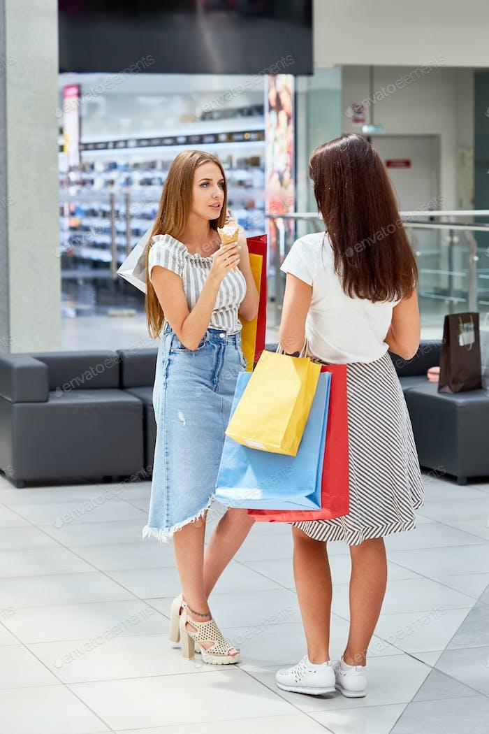 Zwei Mädchen mit Einkaufstaschen Chat