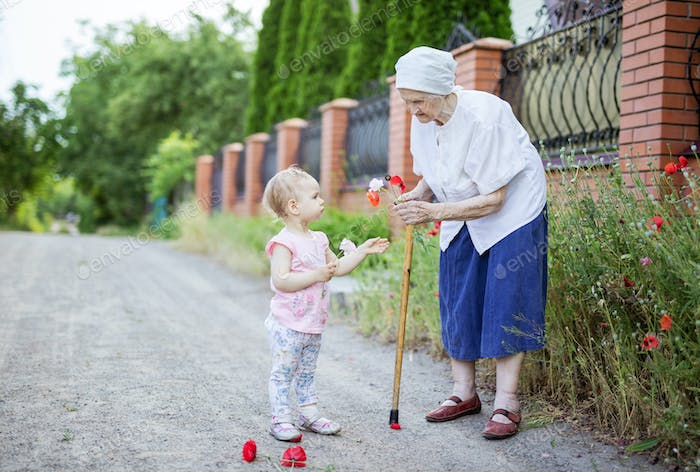 Great grandmother and toddler girl picking flowers outdoors