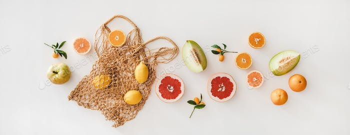 Flat-lay of summer natural net bag and various fresh fruits