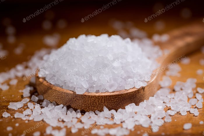 Sea salt crystals closeup in wooden spoon on a kitchen table.