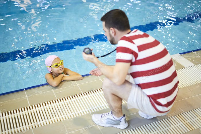 Swim instructor teaching child