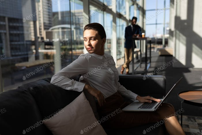 Businesswoman with laptop sitting on the sofa and looking away in modern office