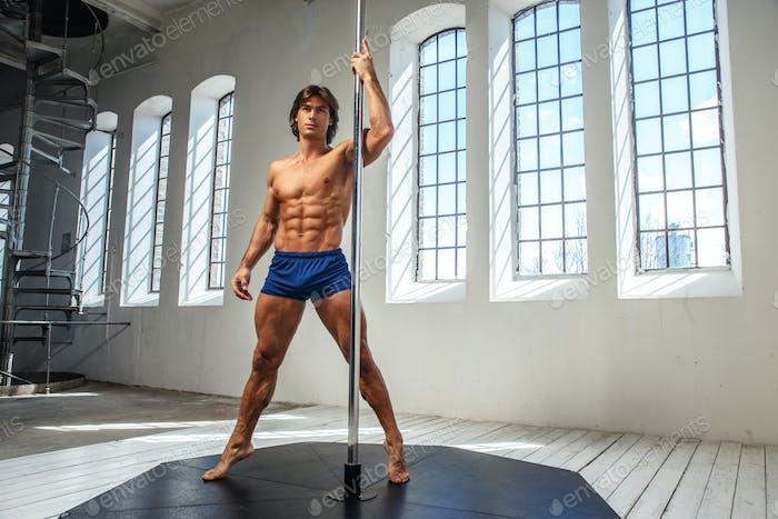 Portrait of sporty male near pole dance stand.