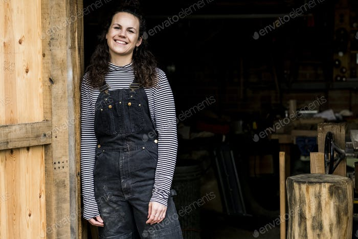 Woman with long brown hair wearing dungarees standing at entrance to wood workshop, smiling at