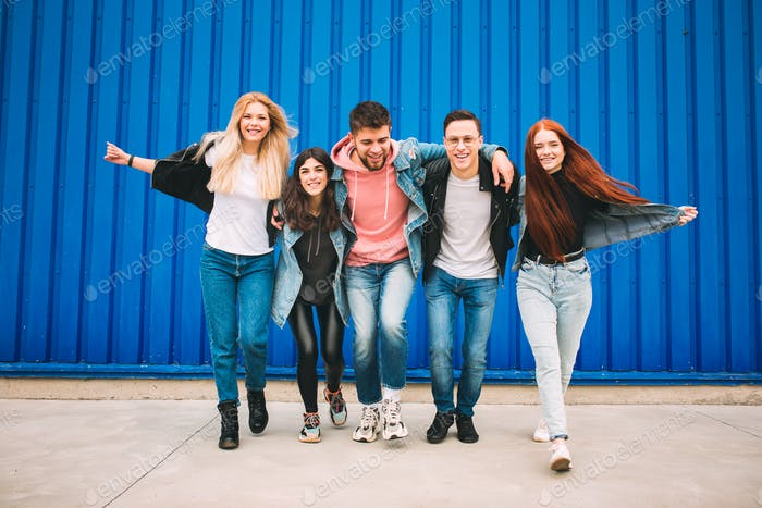 Group of four young diverse friends in jeanse outfit look carefree, young and happy on city's