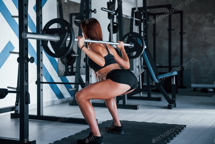 Young fitness woman with slim type of body doing exercises by using barbell