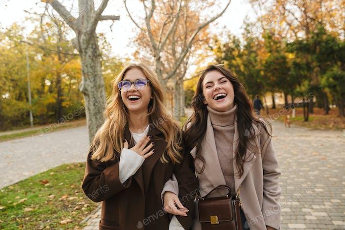 Fröhlich optimistische junge Frauen Freunde zu Fuß