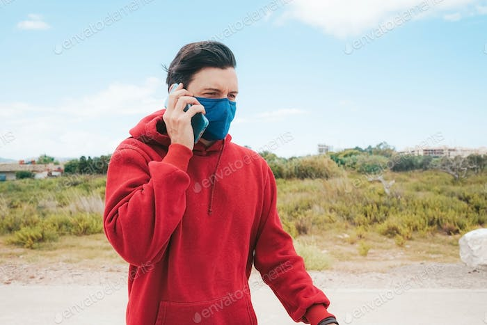 Men using his smartphone with a face mask in Spain