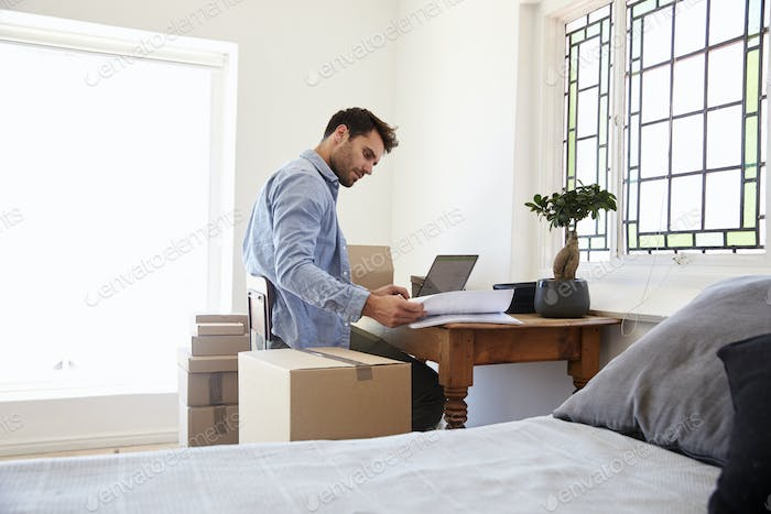 Man In Bedroom Running Business From Home Dispatching Goods