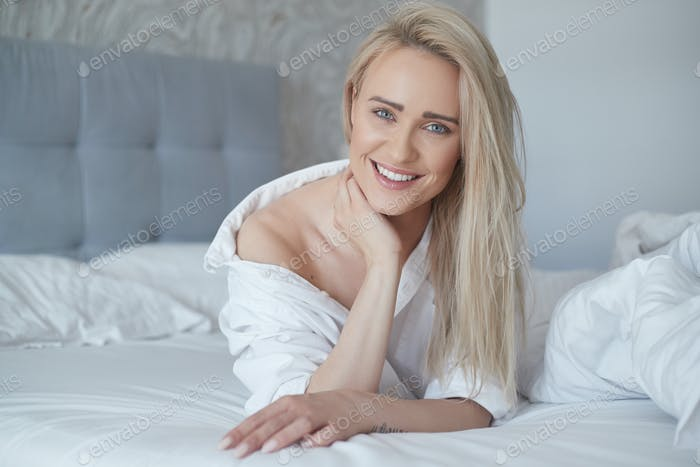 Beautiful middle aged woman lying on the bed, wearing white shirt and smiling