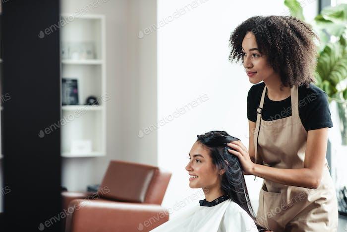 Young brunette enjoying beauty procedures at hairdresser salon