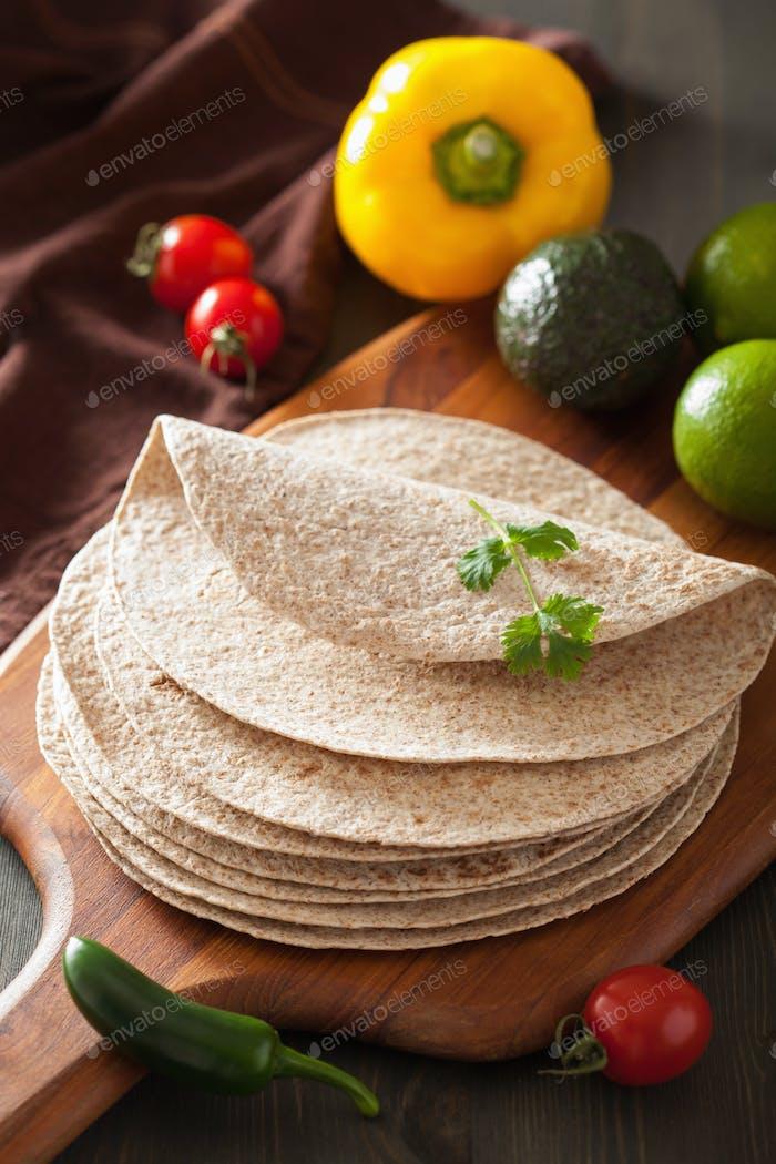 Vollkorn-Tortillas auf Holzbrett und Gemüse