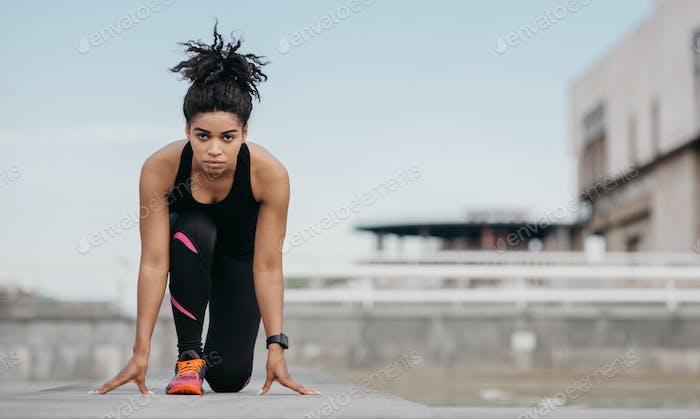 Start training or marathon. Girl in sportswear at start, is ready to run