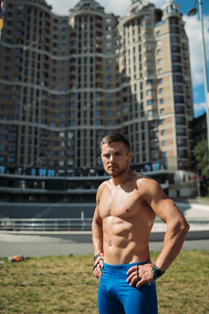 Мускулистый парень с обнаженным туловищем на фоне высокого здания