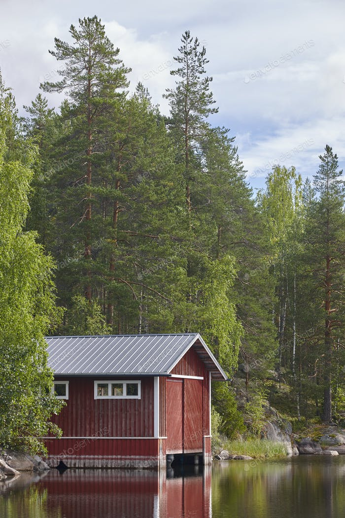 Finland landscape forest lake and red wooden cabin. Finnish summer