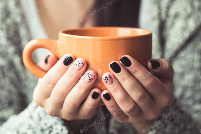 Frau mit schöner Maniküre hält eine orange Tasse Kakao