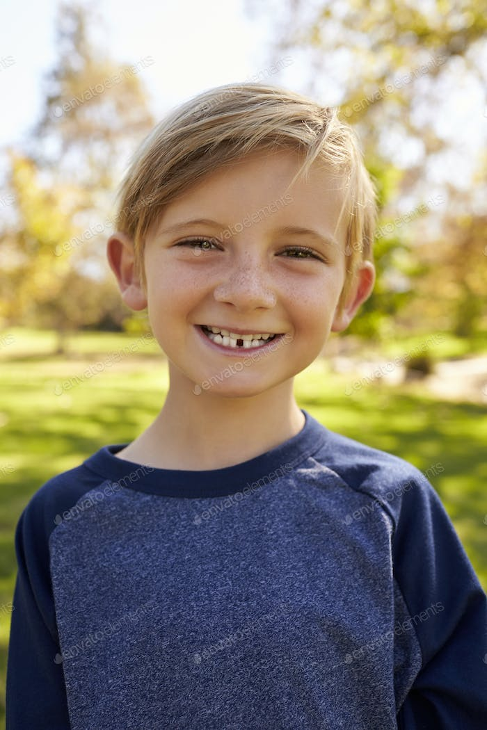 Seven year old Caucasian boy in a park, vertical portrait