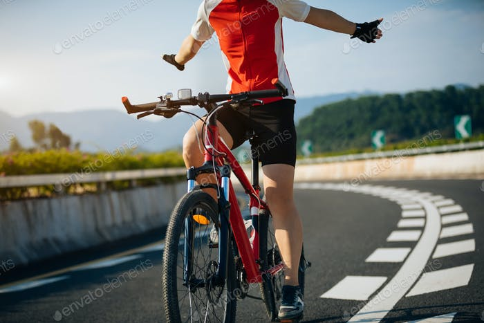 Woman riding bike on highway handsfree